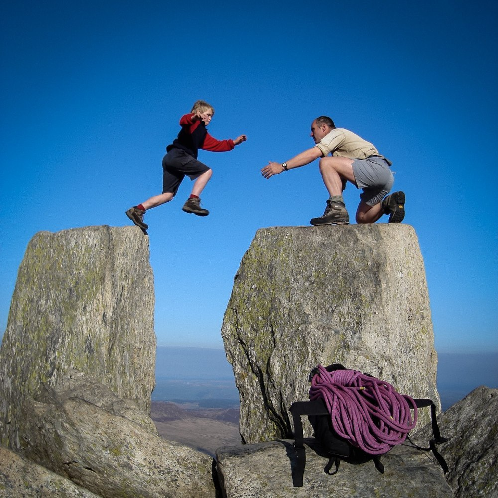 Father helps son jump between rocks