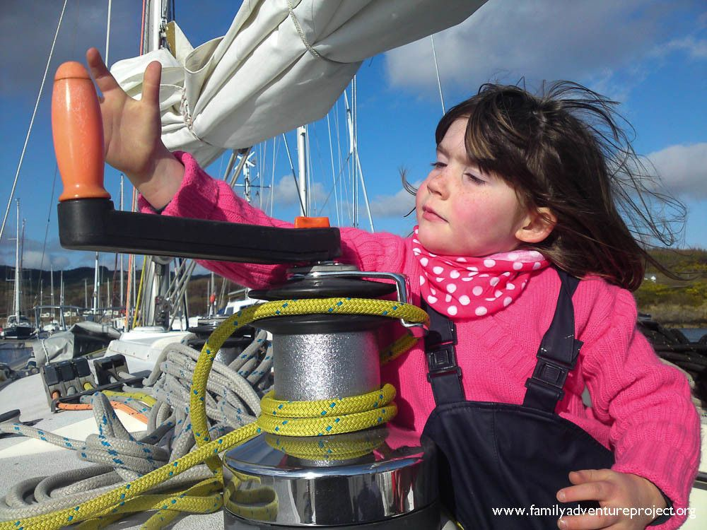 Little girl winching in the sails