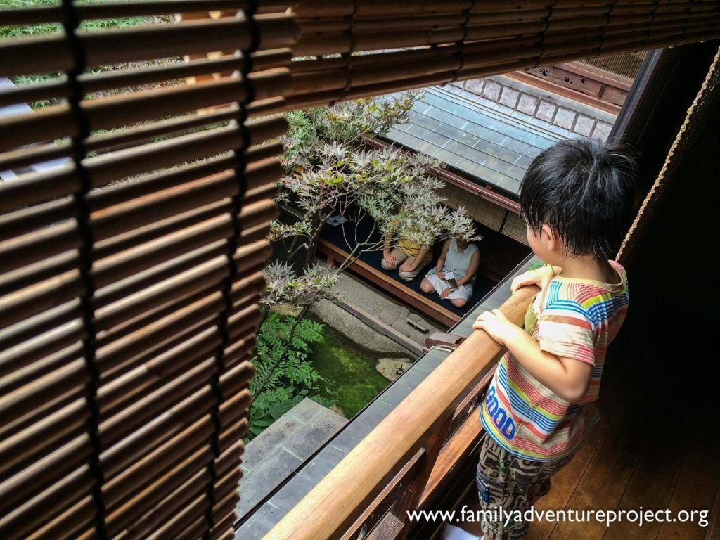 Child watches visitors meditate at the Shima Geisha House, Kanaz