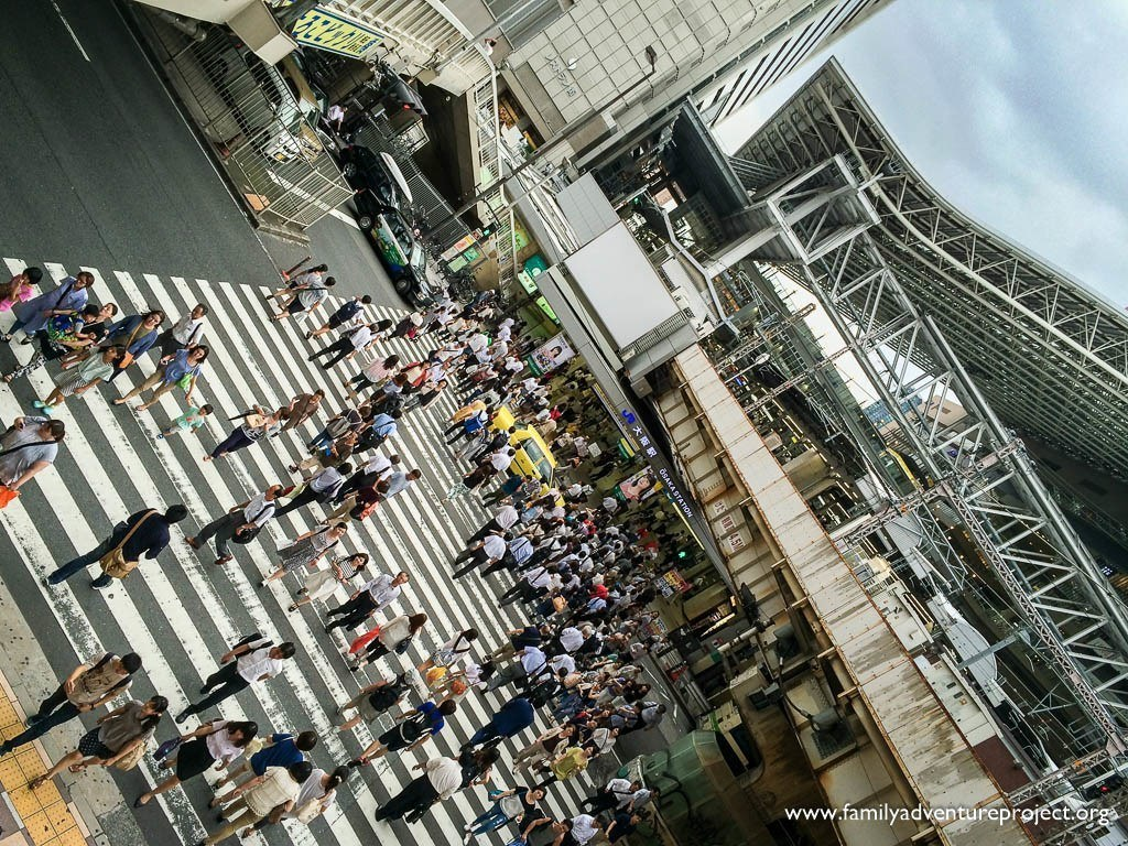 People crossing the road outside Osaka Japan Rail Station