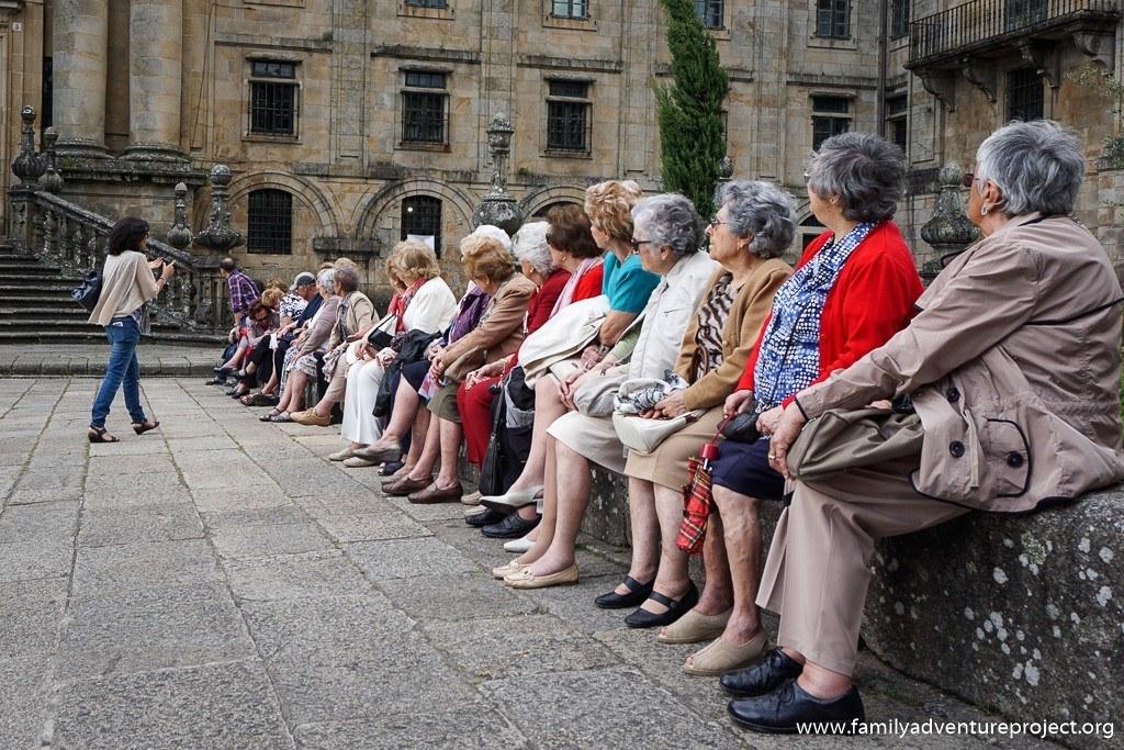 Galicia travel guide talks to tourists outside St Martin Pinario Monastery in Santiago