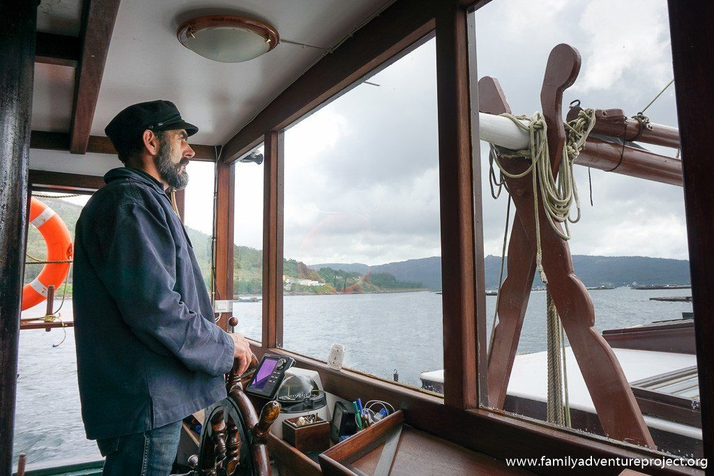 Captain steers the boat on Mussel fishing trip Bay of Muros, Galicia