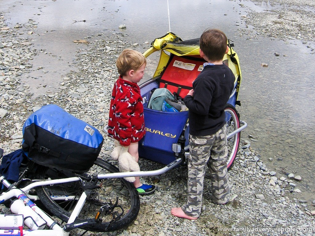 Kids wait by river with cycle trailer. Shoes on and shoes off.