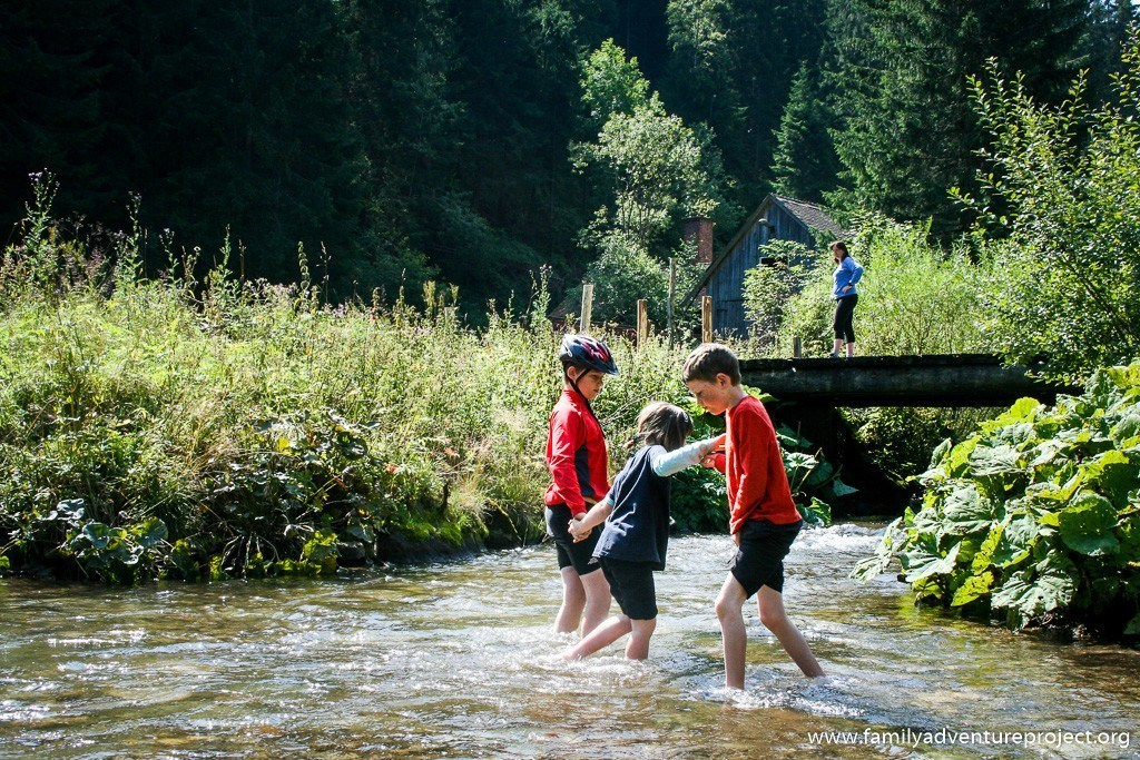 Kids playing in a river while mother watches from a bridge