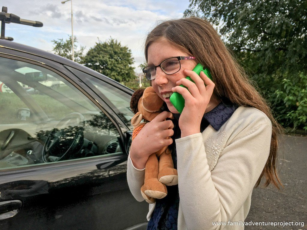 Child using a mobile phone in a car park