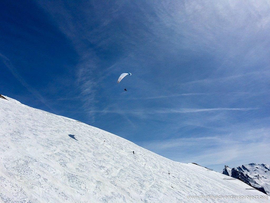Parapenter passes over skier on Mont Lachat, La Clusaz, Haute Savoie, France