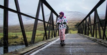 Girl Scooting over bridge in Glen Lyon, Perthshire, Scotland