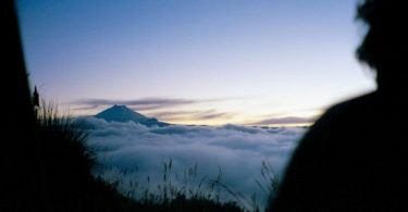 Volcano Cotopaxi seen from above the clouds climbing up into the Andes